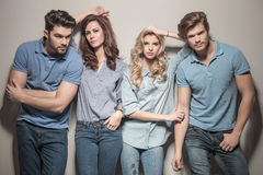 Women leaning against their handsome men. Two couples of young casual people standing together in studio Stock Image