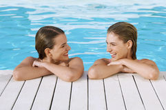 Women Leaning At Poolside. Happy young women looking at each other while leaning at poolside royalty free stock images