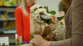 Women learn to make floral design under the guidance of a professional. A group of young women in the class of stock video