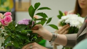 Women learn to make floral design under the guidance of a professional. A group of young women in the class of. Floristics. The practice of making beautiful stock video footage