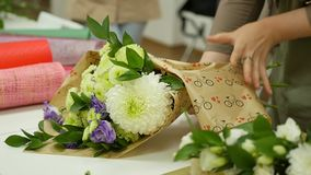 Women learn to make floral design under the guidance of a professional. A group of young women in the class of. Floristics. The practice of making beautiful stock video