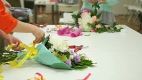 Women learn to make floral design under the guidance of a professional. A group of young women in the class of. Floristics. The practice of making beautiful stock footage