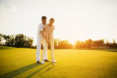 Couple learning to play golf on the golf course against the sunset background Stock Photo
