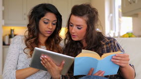Women learning with book and tablet pc. On sofa stock video footage