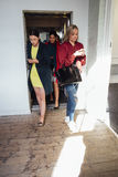 Women Leaving A Lift. Group of workers are leaving a lift to go their workplace. They are all engrossed in their smart phone Royalty Free Stock Images