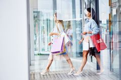 Women Leaving Shopping Center with Paper Bags royalty free stock image