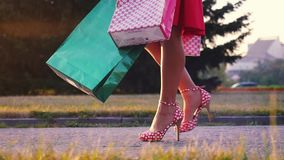 Women leg in beautiful dress with shopping bags goes on the street through the sun during sunset in slowmotion stock video footage