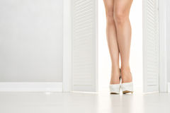 Women leg in white shoe looks out of the open door Stock Photography