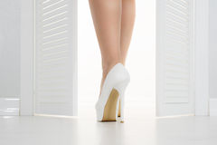 Women leg in white shoe looks out of the open door Stock Photos