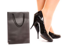 Women legs in fashion shoes near shopping bag Stock Image