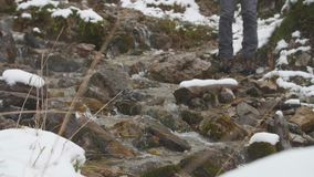 Hiker climbing up a mountain trail. Women legs hiking steep terrain in slow motion on a cold cloudy winter day. Snow falling. Female hiker in trekking boots stock video