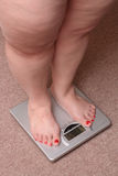 Women legs with overweight. Standing on bathroom scales Stock Photo