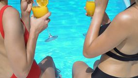 Women with legs in pool clinking and drinking cocktails, summertime leisure. Stock footage stock video footage