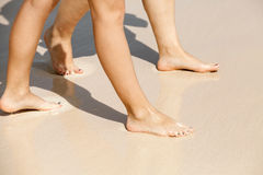 Women legs walk on a wet sandy beach. On the sea coast Royalty Free Stock Image
