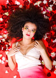 Women lie on the rose petals Stock Images
