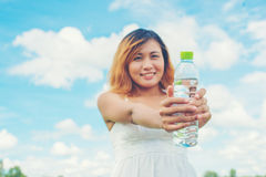 Women lifestyle concept young pretty  woman wearing white dress. Woman wearing white dress holding bottle of water at grassland smiley to camera look so fresh Royalty Free Stock Images