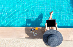 Women lifestyle play laptop relaxing near luxury swimming pool sunbath, summer day at the beach resort in the hotel. stock photo