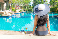 Women lifestyle relaxing near luxury swimming pool sunbath, summer day at the beach resort in the hotel. Royalty Free Stock Images