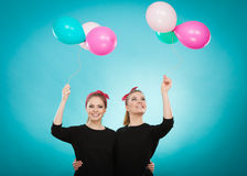 Women like a little girls want fly away by balloons. Stock Photo
