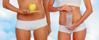 Women in lingerie with an apple and a bottle of water Stock Photos