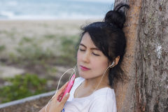 Women listen to music from a mobile. Cute woman listening to music with mobile and happy Stock Image