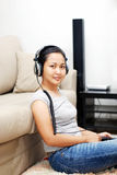 Women listening to headphone. In living room Royalty Free Stock Photo