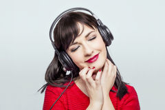 Women listening to music. Pretty lady listening to music over headphones Stock Images