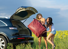 Women loading a heavy bag into car. Two women tourists loading a heavy bag into the back of an estate car with the boot open near a field of sunflowers royalty free stock photos