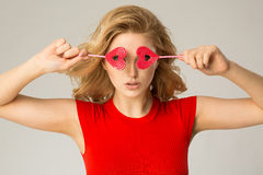 Women with lollypops on eyes. Royalty Free Stock Photos