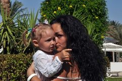 A woman with long, black curly hair embraces her daughter on a sunny day. stock photos