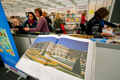 Women look at new art books at the indoor book fair stock images