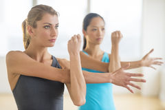 Women Looking Away While Doing Stretching Exercise Royalty Free Stock Photos