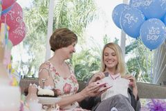 Women Looking At Baby Clothes. Mother showing baby clothes to pregnant women at a baby shower stock images