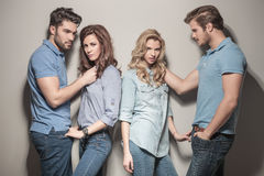 Women looking at the camera near boyfriends. Casual fashion women looking at the camera while the boys are looking away Royalty Free Stock Photos