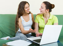 Women looking financial documents with laptop Royalty Free Stock Photography