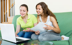 Women looking financial documents with laptop. Smiling european women looking financial documents with laptop  in home interior Royalty Free Stock Image