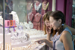 Women looking jewelry counter Stock Images