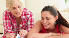 Women looking through magazine and smiling. In living room stock footage