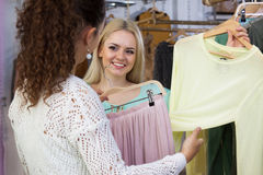 Women looking for new garments. Two women looking for new garments at the store royalty free stock photography
