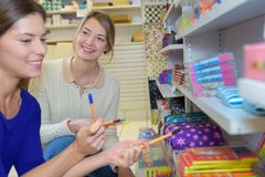 Women looking at pens in stationery shop royalty free stock photography