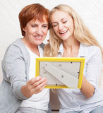 Women looking at photo frame Stock Images