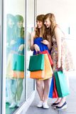 Women looking in shop window royalty free stock images