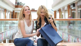 Women looking into shopping bags. Happy young women looking into shopping bags stock footage