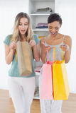 Women looking into shopping bags at home Royalty Free Stock Photography