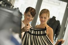 Women looking at a skirt at a boutique. 2 women looking at a skirt at a boutique Stock Photos