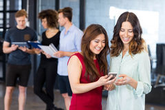 Women looking at smartphone and having discussion Stock Photos