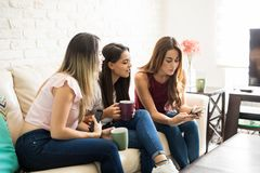 Women looking at a smartphone. Young women showing a photo on her smartphone to her friends while they drink some coffee at home Royalty Free Stock Photography