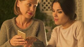 Women looking at social network page of their friends, discussing rumors closeup