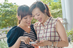 Women looking at something on a cellphone. Group of smiling Asian women looking at something on a cellphone Royalty Free Stock Images
