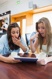 Women looking surprised while holding a tablet Stock Image